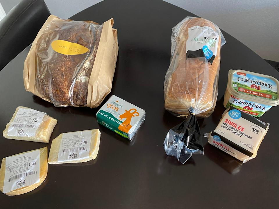 two sets of bread, cheese, and butter sitting on a kitchen table