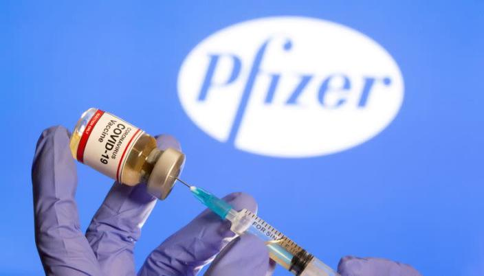 FILE PHOTO: A woman holds a small bottle labeled with a 'Coronavirus COVID-19 Vaccine' sticker and a medical syringe in front of displayed Pfizer logo in this illustration