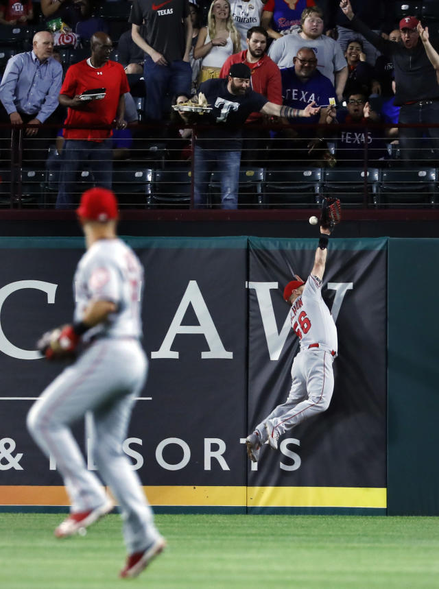 Los Angeles Angels second baseman Tommy La Stella watches as the ball glances off the glove of right fielder Kole Calhoun and falls behind the wall for a two-run home run by Texas Rangers' Asdrubal Cabrera diromg the fourth inning of a baseball game in Arlington, Texas, Tuesday, April 16, 2019. (AP Photo/Tony Gutierrez)