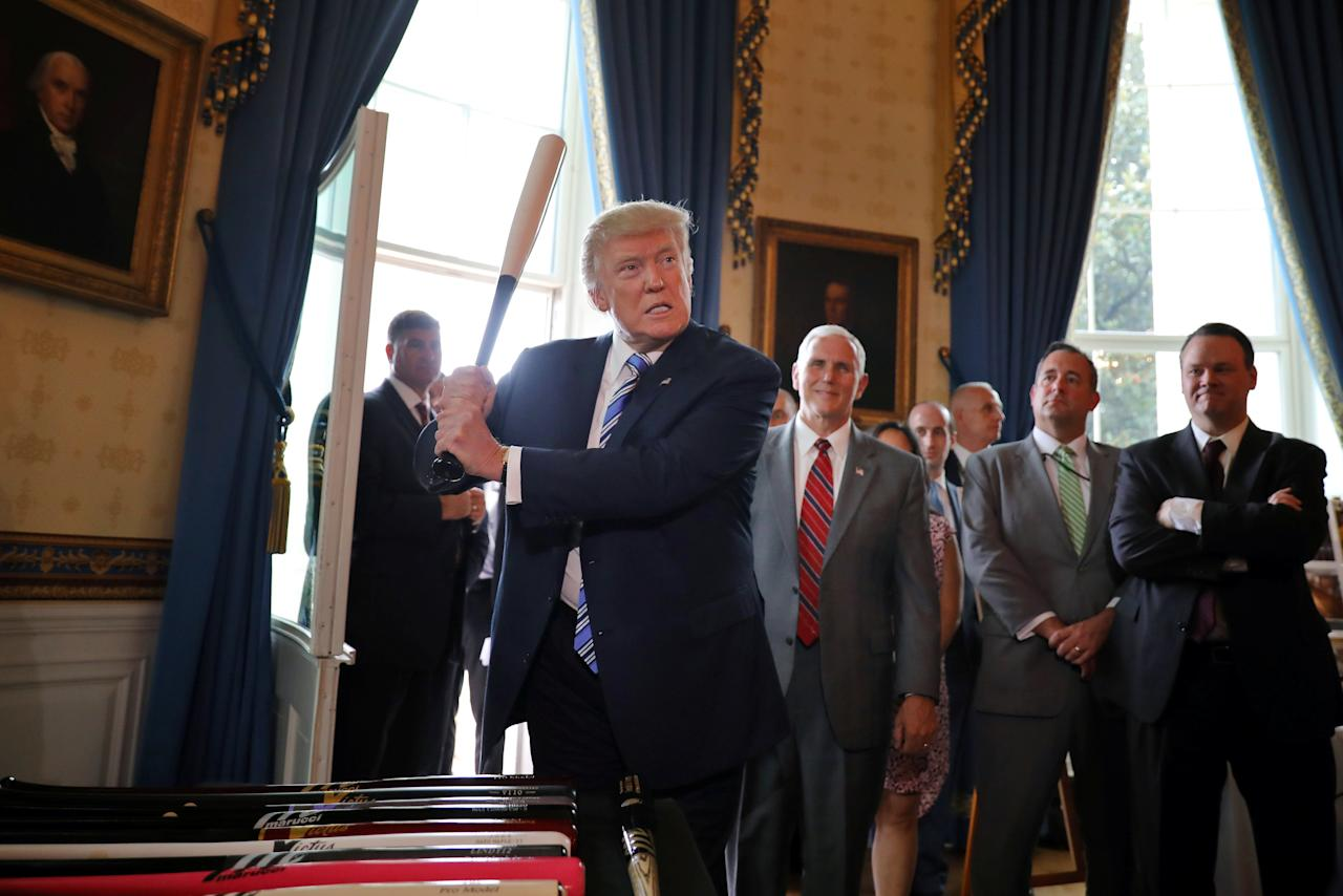 U.S. President Donald Trump reacts as he holds a baseball bat as he participates in a Made in America product showcase at the White House in Washington, U.S., July 17, 2017. REUTERS/Carlos Barria