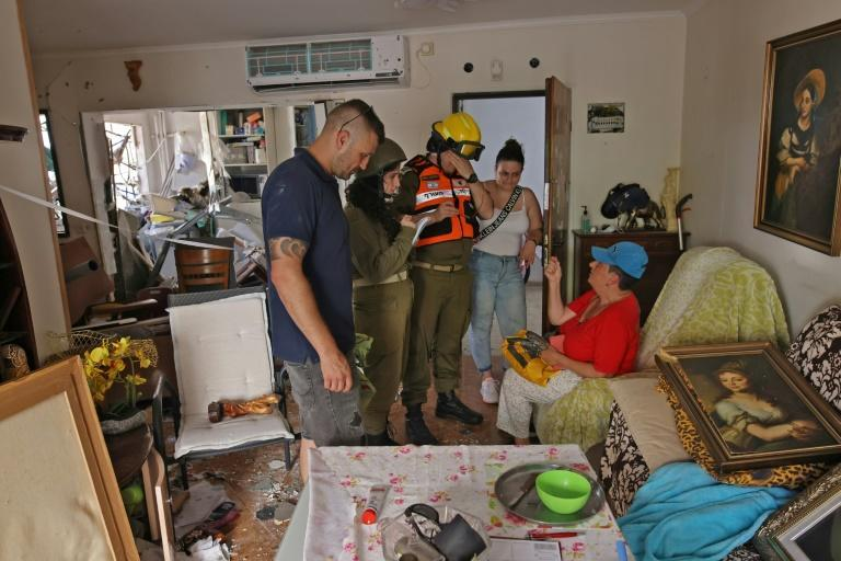An Israeli woman speaks to emergency services inside her damaged apartment that was hit by a rocket launched from the Gaza Strip