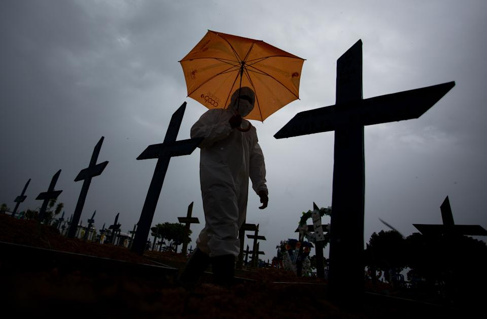 TOPSHOT - A workers wearing a protective suit and carrying an umbrella walks past the graves of COVID-19 victims at the Nossa Senhora Aparecida cemetery, in Manaus, Brazil, on February 25, 2021. - Brazil surpassed 250,000 deaths due to COVID-19. (Photo by MICHAEL DANTAS / AFP) (Photo by MICHAEL DANTAS/AFP via Getty Images)
