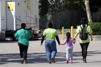 A child holds hands with workers at an emergency shelter for migrant children Friday, July 2, 2021, in Pomona, Calif. The Biden administration on Friday gave a rare look inside an emergency shelter it opened to house migrant children crossing the U.S.-Mexico border alone, calling the California facility a model among its large-scale sites, some of which have been plagued by complaints. (AP Photo/Marcio Jose Sanchez, Pool)