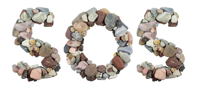 SOS word spelled with pebbles. (Source: Getty Images)