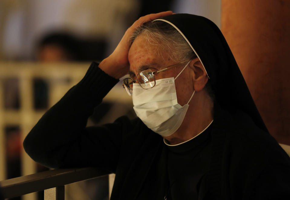 A nun wears a mask to protect from COVID-19, as she attends a Good Friday Mass for the Passion of Christ, at a church in Beirut, Lebanon, Friday, April 2, 2021. Christians in Lebanon observed Good Friday under a COVID-19 lockdown and amid a severe economic crisis exacerbated by the massive explosion that demolished parts of the capital last year. Even traditional Easter sweets are a luxury few can afford. (AP Photo/Hussein Malla)