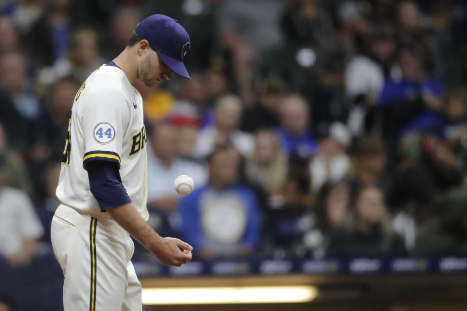 Milwaukee Brewers' Jake Cousins tosses the ball as he walks back to the mound after a run-scoring wild pitch during the fifth inning of a baseball game against the Cincinnati Reds Thursday, July 8, 2021, in Milwaukee. (AP Photo/Aaron Gash)