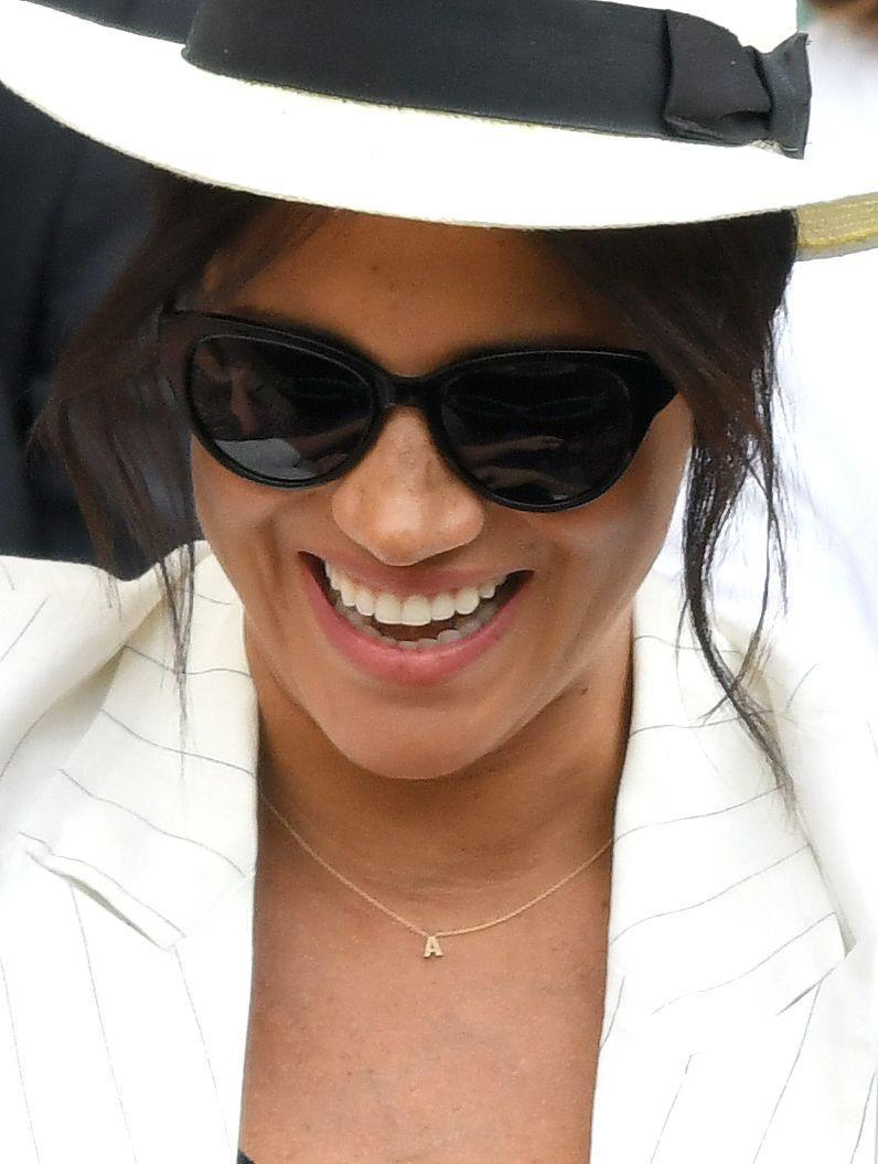 """<p>Meghan has quite the collection of symbolic yet simple gold necklaces. She wore a tiny """"A"""" necklace to Wimbledon in 2019 as a nod to her son, Archie. <br></p>"""