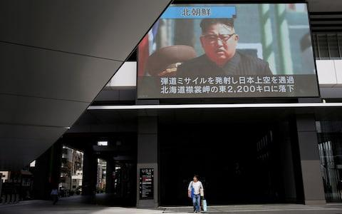 A passerby walks under a TV screen reporting news about North Korea's missile launch in Tokyo - Credit: Reuters