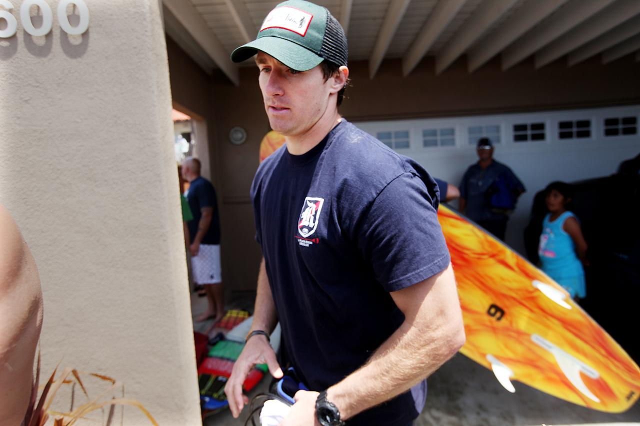 "OCEANSIDE, CA - MAY 6: New Orleans Saints Quarterback Drew Brees walks out after a ""paddle out"" in honor of NFL star Junior Seau on May 6, 2012 in Oceanside, California.  Seau, who played for various NFL teams including the San Diego Chargers, Miami Dolphins and New England Patriots was found dead in his home on May 2nd of an apparent suicide.  Family members have decided to donate his brain for research on links between concussions and possible depression. (Photo by Sandy Huffaker/Getty Images)"
