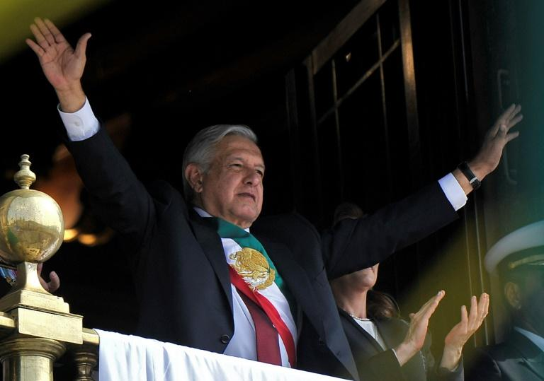 Mexican President Andres Manuel Lopez Obrador waves from the balcony of the National Palace during the anniversary of the Mexican Revolution in Mexico City on November 20