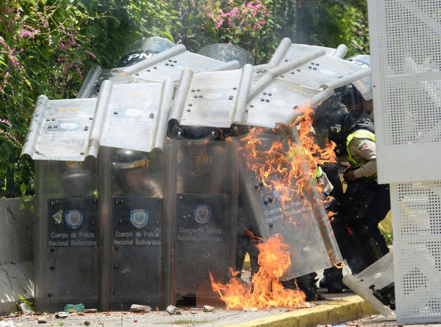 <p>Riot police protect themselves with their shields after students of the Central University of Venezuela thrown them molotov coctels during a protest against Venezuelan Government in Caracas on May 4, 2017. (Photo: FEDERICO PARRA/AFP/Getty Images) </p>