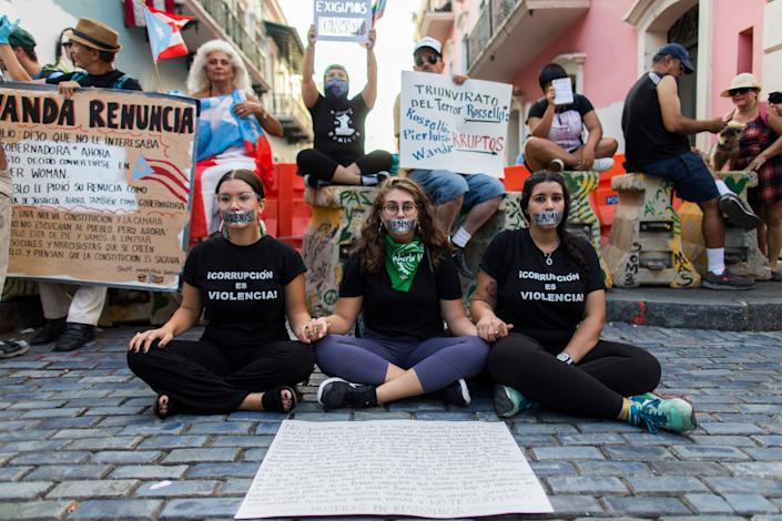 Three women sit with their mouths taped shut outside the government mansion La Fortaleza, where a small group of protesters gathered in San Juan, Puerto Rico, on Aug. 9, 2019. (Photo: Dennis M. Rivera Pichardo/AP)