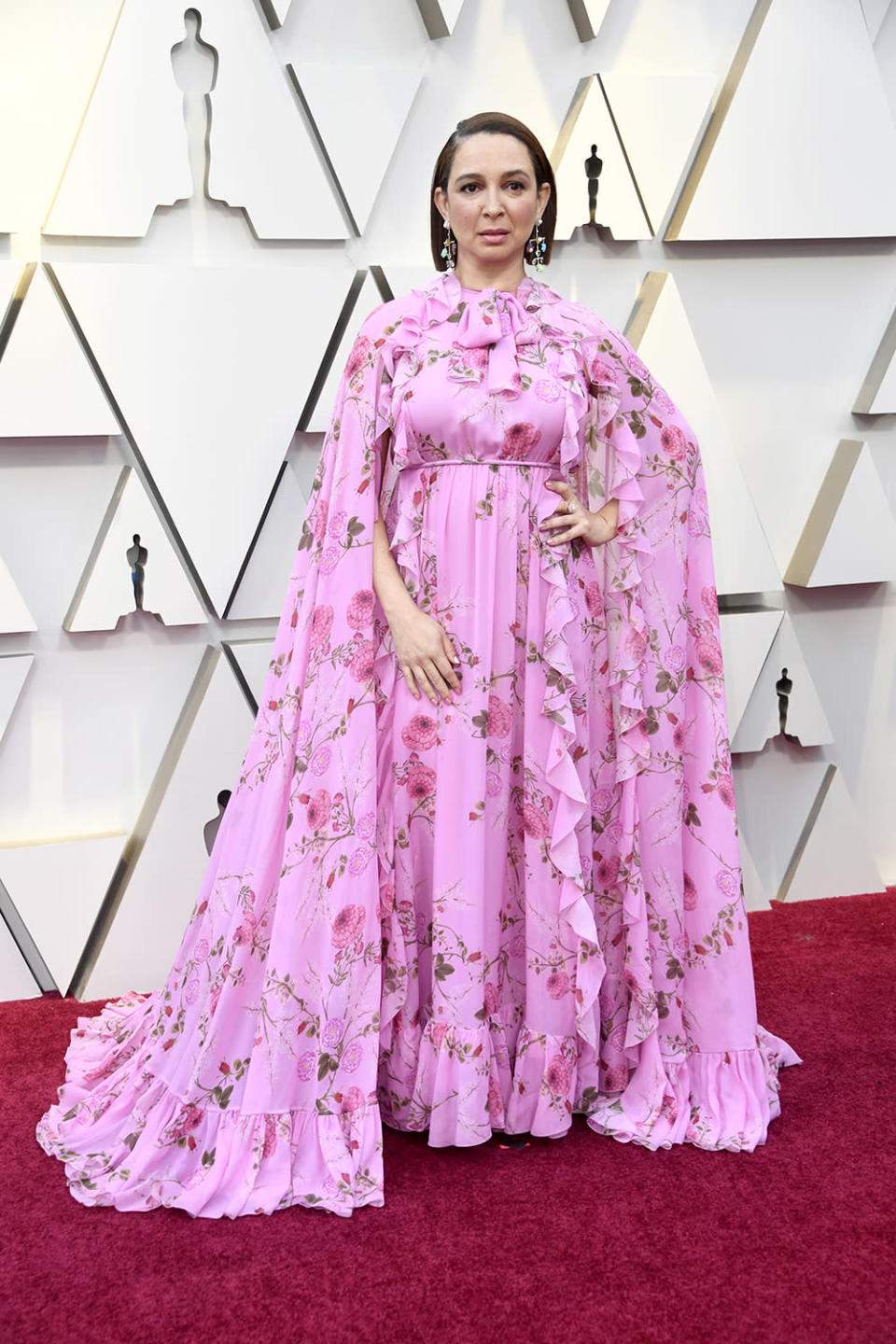 <p>The 'Bridesmaids' star added some print to her pink look, wearing a caped, floral dress to the Academy Awards. <em>[Photo: Getty]</em> </p>