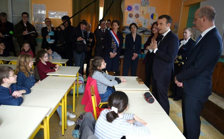 French President Emmanuel Macron is watched by French minister of National Education, Jean-Michel Blanquer as he interacts with children during a visit to the primary school of Rilly-sur-Vienne in central France