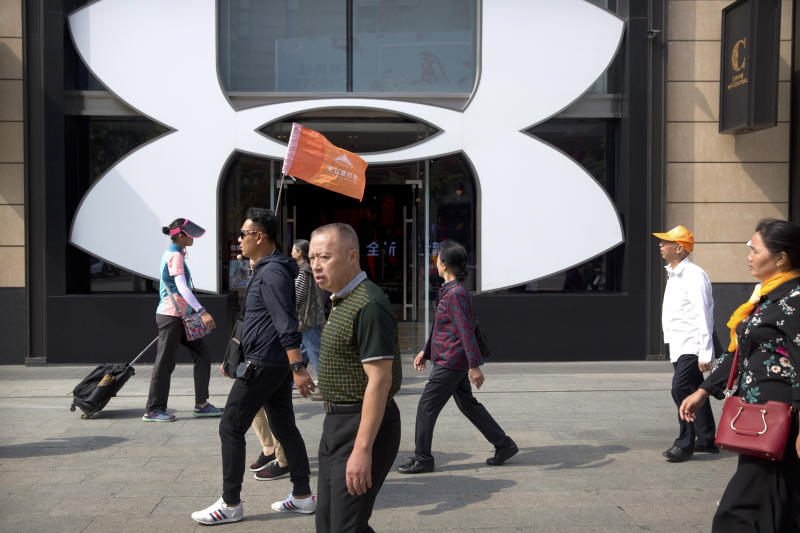 """A Chinese tour guide leads a tour group past a store from American sportswear retailer Under Armour at an outdoor shopping area in Beijing, Tuesday, Sept. 25, 2018. A Chinese trade envoy said Tuesday that talks with Washington are impossible while the United States """"holds a knife"""" to Beijing's neck by imposing tariff hikes. (AP Photo/Mark Schiefelbein)"""