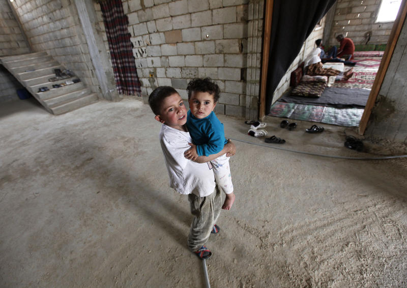 FILE - In this May 29, 2012 file photo, a Syrian refugee boy Nahar al-Nahar, 9, carries his relative, Mounir, 18 months, who fled their houses from Bab Dreib neighborhood in Homs province, walks at an under construction home which they took with their families temporarily, at the Lebanese-Syrian border town of Arssal, eastern Lebanon. A housing unit designed for the United Nations' refugee agency to offer shelter for those, fleeing conflict has become the latest source of friction between Lebanese politicians and aid organizations trying to manage the massive number of Syrian refugees in the country. Lebanon's refusal to set up any kind of organized accommodation for tens of thousands of Syrians, including refugee camps. (AP Photo/Hussein Malla, File)