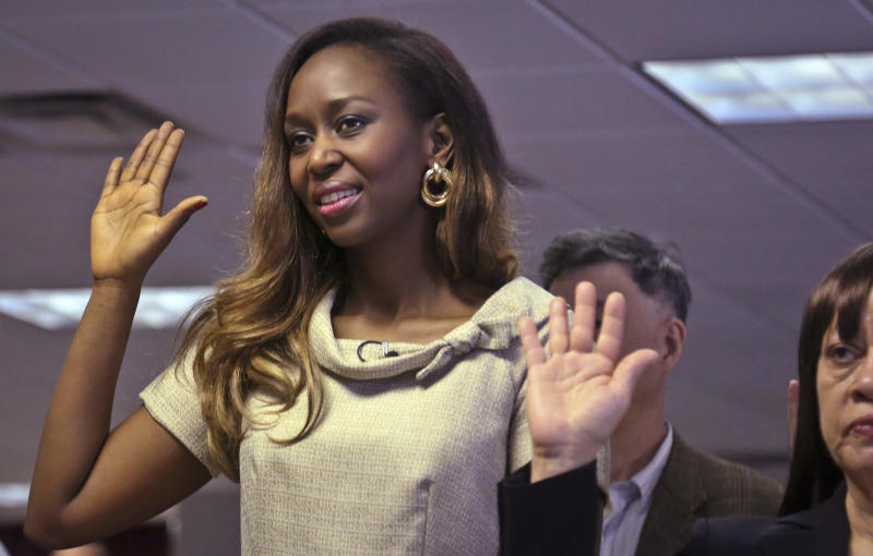 "Immaculee Ilibagiza raises her right hand along with 50 new citizens as she says the oath of citizenship, during a naturalization ceremony at the U.S. Citizenship and Immigration Services  on Wednesday, April 17, 2013, in New York.  ""Who would know that this fantasy would finally happen,"" said Ilibagiza, author of the best seller ""Left to Tell, Discovering God Amidst the Rwandan Holocaust.""  She sought asylum in the U.S. after fleeing the 1994 Rwandan genocide, which claimed more than 500,000 lives.  (AP Photo/Bebeto Matthews)"