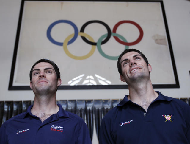 In this May 7, 2012, shows American Olympic rowers Ross James, left, and his twin brother, Grant James, right, pose next to an Olympic flag at the rowing office in Oakland, Calif. Both will be competing in the London Olympics. (AP Photo/Paul Sakuma)