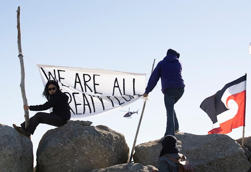 "Sipekne'katik First Nation community members waved a flag that said, ""We are all treaty people,"" while a coast guard helicopter hovered in the background in Saulnierville, N.S., on Sept. 20, 2020. (Photo: Mark O'Neill/The Canadian Press)"