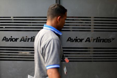 A man walks past corporate logos of Avior Airlines at their office in Caracas, Venezuela May 15, 2019. REUTERS/Manaure Quintero NO RESALES. NO ARCHIVES.