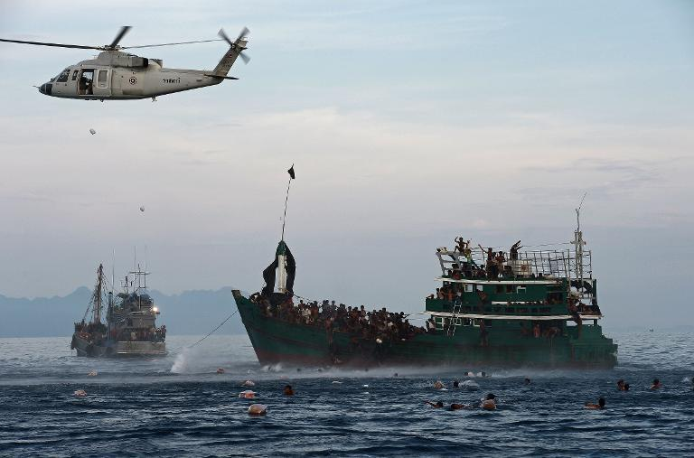 Rohingya migrants swimming to collect food supplies dropped by a Thai army helicopter after they jumped from a boat (R) drifting in Thai waters off the southern island of Koh Lipe in the Andaman sea