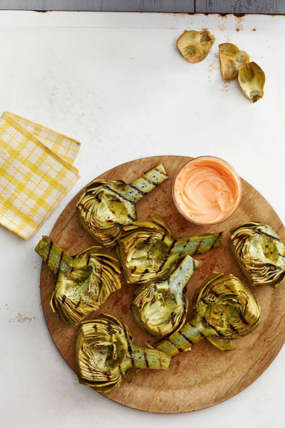 "A little sweet, smoky, and spicy, these simple grilled artichokes make an unexpectedly delicious appetizer or party dish. <a href=""https://www.countryliving.com/food-drinks/recipes/a5136/grilled-artichokes-harissa-honey-dip-recipe-clx0514/"" rel=""nofollow noopener"" target=""_blank"" data-ylk=""slk:Get the recipe."" class=""link rapid-noclick-resp""><strong>Get the recipe.</strong></a>"