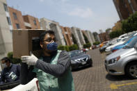 A city workers carries a food supply kit during home deliveries to households with a member suffering from symptoms of COVID-19, in the Coyoacan district of Mexico City, Thursday, April 9, 2020. To help halt the spread of the new coronavirus, the Mexican megalopolis is making home deliveries to households with a symptomatic person, providing kits containing food staples, face masks, gloves, antibacterial gel, paracetamol, a thermometer, and benefits cards with a balance of 1000 pesos (around $42). (AP Photo/Rebecca Blackwell)