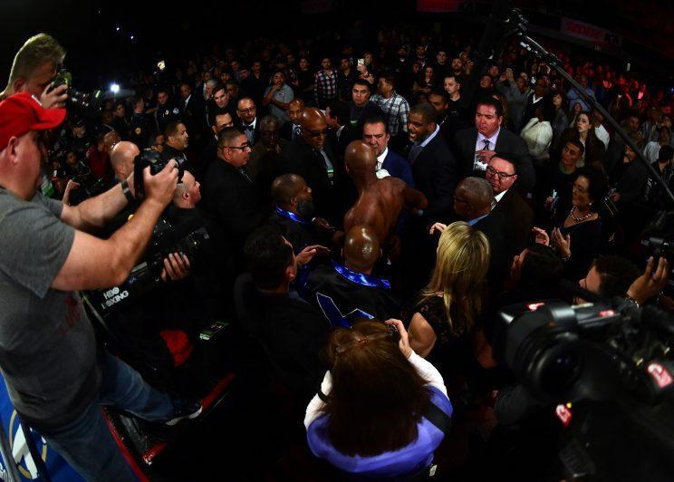 Bernard Hopkins arises amid a sea of people at ringside after getting knocked through the ropes in the eighth round Saturday by Joe Smith Jr. (Getty Images)