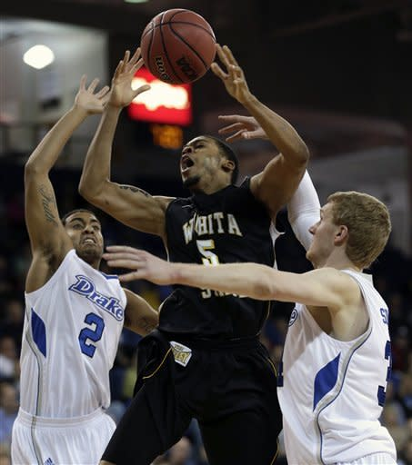 Wichita State guard Demetric Williams, center, is fouled as he drives to the basket between Drake's Gary Ricks Jr., left, and Ben Simons, right, during the first half of an NCAA college basketball game on Wednesday, Jan. 2, 2013, in Des Moines, Iowa. (AP Photo/Charlie Neibergall)