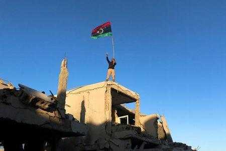 A fighter of Libyan forces allied with the U.N.-backed government waving a Libyan flag flashes victory sign as he stands atop the ruins of a house after forces finished clearing Ghiza Bahriya, the final district of the former Islamic State stronghold of Sirte, Libya December 6, 2016. REUTERS/Hani Amara/Files