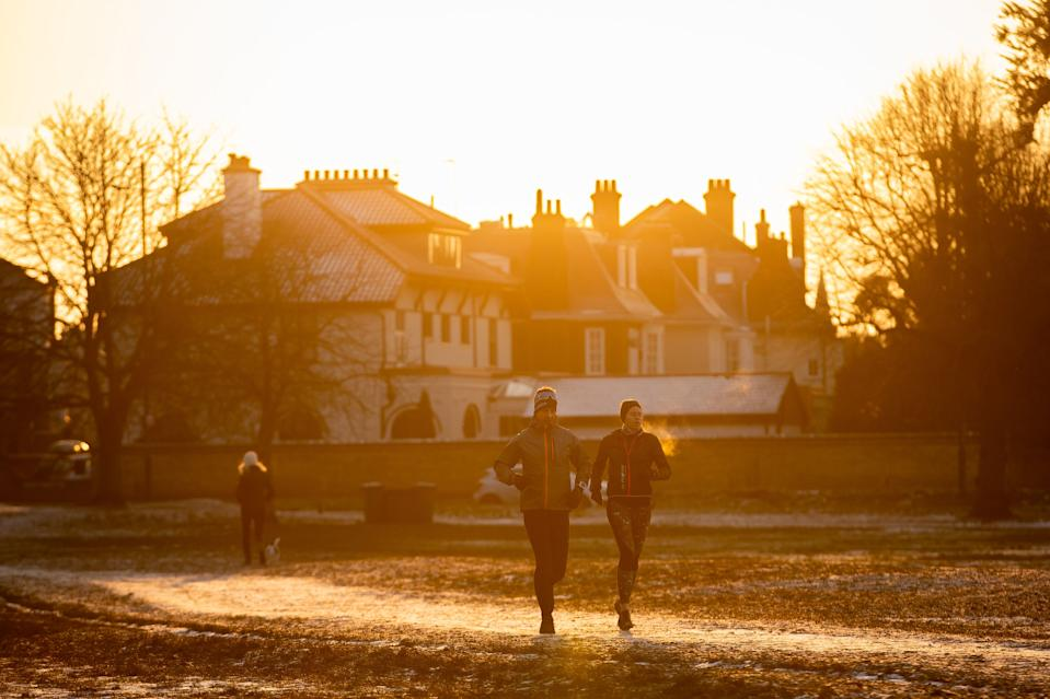 People out on a morning run near a frozen Rushmere Pond at Wimbledon Common, south London, as the cold snap continues to grip much of the nation. Picture date: Thursday February 11, 2021. (Photo by Aaron Chown/PA Images via Getty Images)