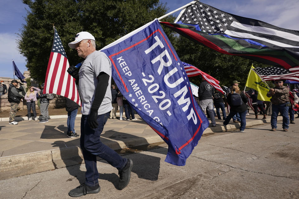 A supporter of President Donald Trump walks with flags near the Texas State Capitol during a rally, Saturday, Jan. 9, 2021, in Austin, Texas. (AP Photo/Eric Gay)