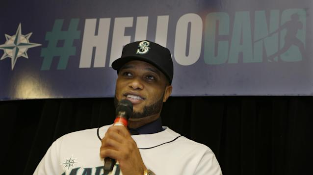 "Robinson Cano sits under a sign that reads ""#HelloCano"" as he talks to fans gathered at an event to honor him as the newest member of the Seattle Mariners baseball team on Thursday, Dec. 12, 2013, in Seattle. (AP Photo/Ted S. Warren)"