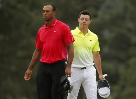 FILE PHOTO: Woods of the U.S. and McIlroy of Northern Ireland finish their round on the 18th green during the final round of the Masters golf tournament at the Augusta National Golf Course in Augusta