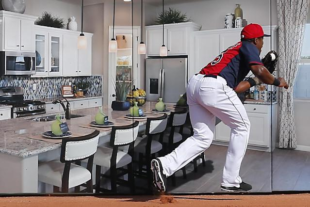 Cleveland Indians right fielder Carlos Moncrief catches a fly ball hit by Cincinnati Reds' Kristopher Negron at the right field wall in the seventh inning of an exhibition baseball game in Goodyear, Ariz., Wednesday, Feb. 26, 2014. The wall displays an advertisement for a homebuilder. (AP Photo/Paul Sancya)