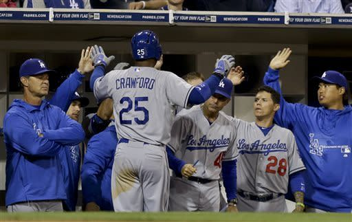 Los Angeles Dodgers' Carl Crawford is congratulated at the dugout after scoring from third on a hit by Mark Ellis during the fifth inning of a baseball game against the San Diego Padres in San Diego, Wednesday, April 10, 2013. (AP Photo/Lenny Ignelzi)