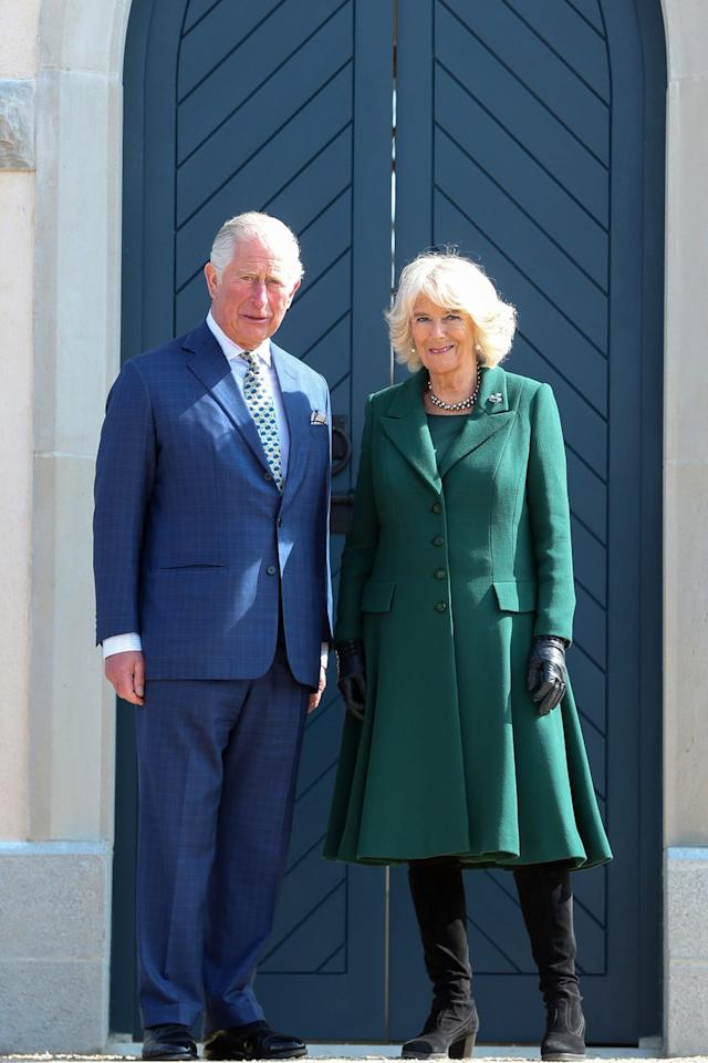 """<p>Camilla wore a green coat dress for her <a href=""""https://www.townandcountrymag.com/society/tradition/a27088939/prince-charles-camilla-wedding-anniverary-northern-ireland/"""" target=""""_blank"""">trip to Northern Ireland with Prince Charles</a>. The royal topped off the look with black boots and gloves, pearl drop earrings, a choker necklace of black pearls, and an emerald and diamond shamrock brooch. </p>"""
