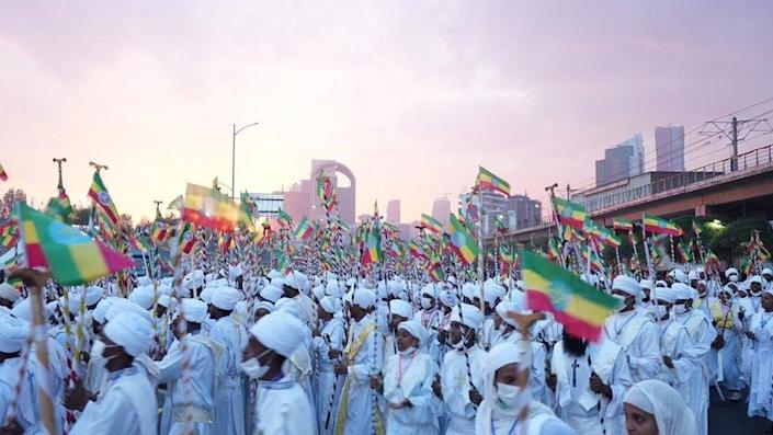Crowd dressed in white with Ethiopian flags