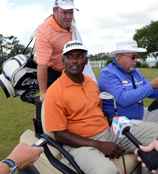 """Vijay Singh sits in a cart driven by Doug Kidd, of TPC Sawgass Golf Operations after his practice round at The Players Championship golf tournament Wednesday, May 8, 2013, in Ponte Vedra Beach, Fla. Singh sued the PGA Tour on Wednesday for exposing him to """"public humiliation and ridicule"""" during a 12-week investigation into his use of deer antler spray that ended last week when the tour dropped its case against him. (AP Photo/The Florida Times-Union, Bob Mack)"""