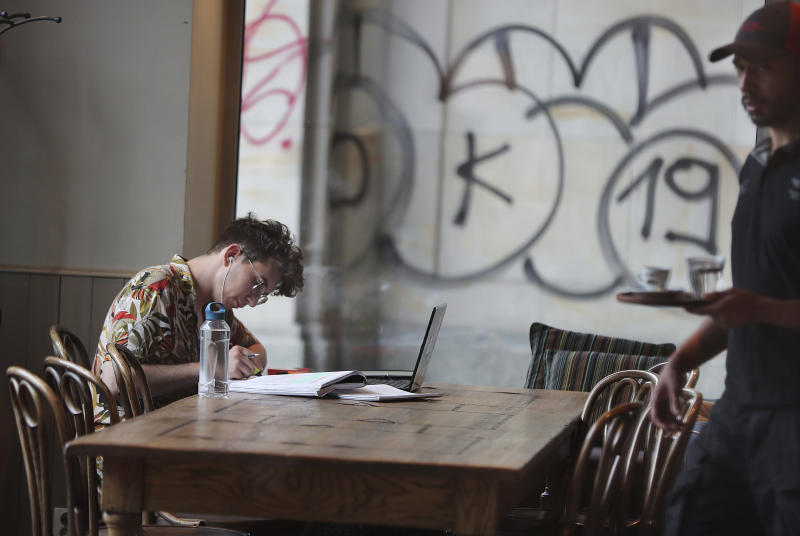 A Polish man works in a cafe in Warsaw, Poland, Thursday, Aug. 1, 2019.  Poland on Thursday scrapped its personal income tax for young employees earning less than dollars 22,000 a year, as part of a drive to reverse a brain drain and demographic decline that's dimming the prospects of a country that is otherwise experiencing strong economic growth.(AP Photo/Czarek Sokolowski)