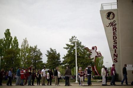 Redskin fans wait in line outside the FedEx Field stadium before the start of a draft day party in Landover