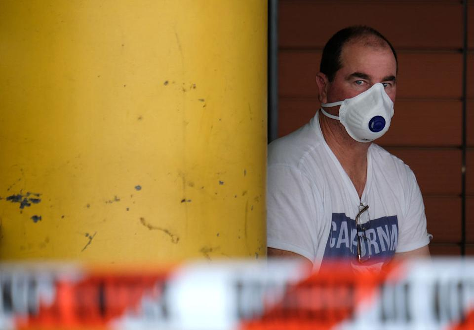 A man wearing a mask waits in a line to be screened for coronavirus outside the Royal Melbourne Hospital.