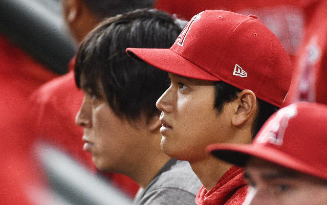 Los Angeles Angels' Shohei Ohtani, right, watches from the dugout during the seventh inning of a baseball game against the Houston Astros, Monday, April 23, 2018, in Houston. (AP Photo/Eric Christian Smith)