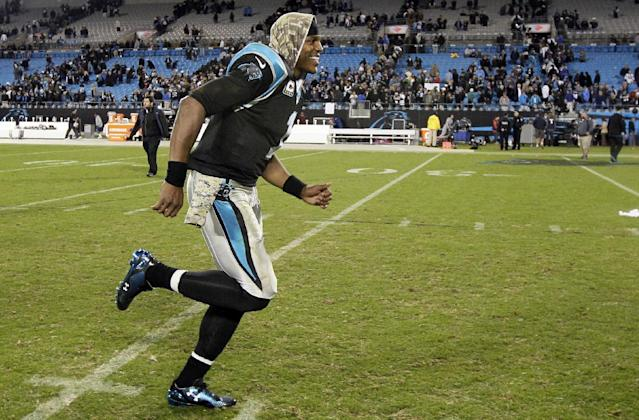 Carolina Panthers quarterback Cam Newton smiles as he runs off the field following Carolina's 24-20 win over the New England Patriots following an NFL football game in Charlotte, N.C., Monday, Nov. 18, 2013. (AP Photo/Gerry Broome)