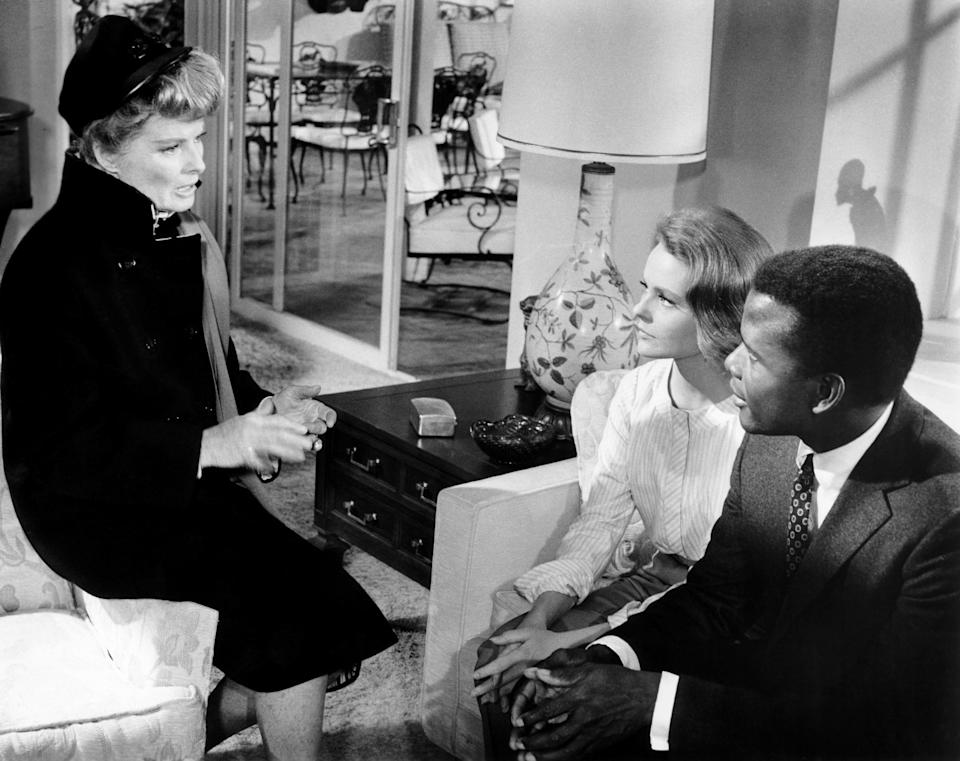 Katharine Hepburn sits on a chair talking to Katharine Houghton and Sidney Poitier on a couch