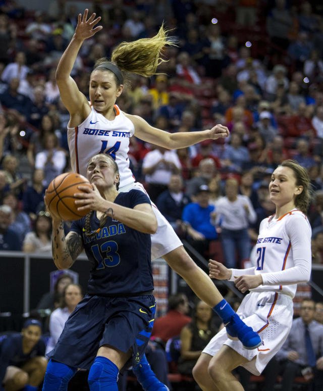 Nevada guard T Moe (13) attempts to shoot under tight defense by Boise State guard Braydey Hodgins (14) during the last quarter of an NCAA college basketball women's championship game in the Mountain West Conference tournament Friday, March 9, 2018, in Las Vegas. (AP Photo/L.E. Baskow)