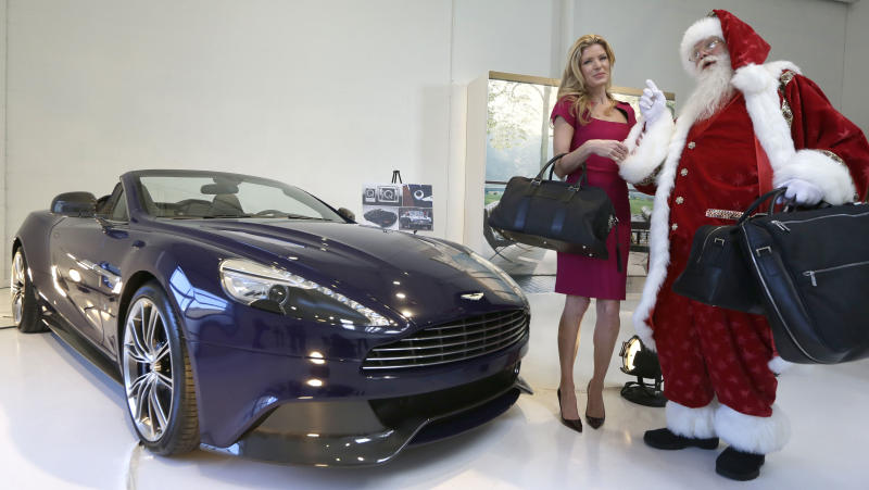 Actor Brady White, right, portrays Santa Claus as he and model Lesley Heaton show off the 2014 Aston Martin Vanquish Volante during the unveiling of the gifts included in the Neiman Marcus Christmas Book Tuesday, Oct. 8, 2013, in Dallas. The special edition Aston Martin is on sale for $344,5000 (AP Photo/LM Otero)
