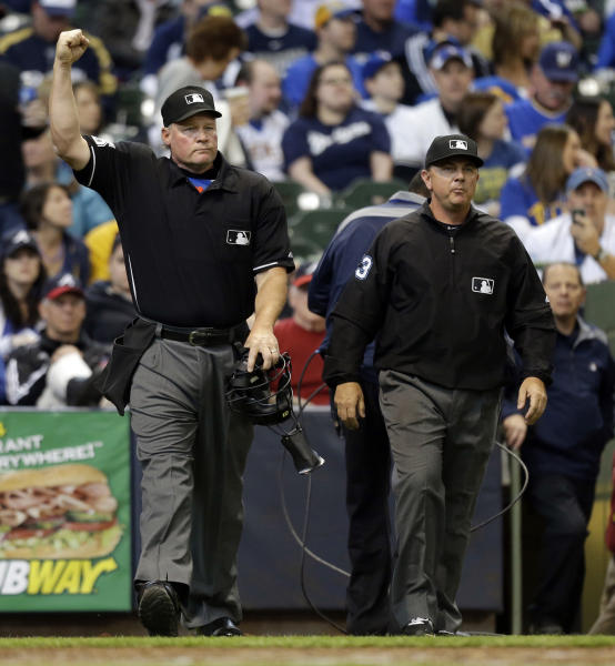Umpire Ted Barrett, left, signals an out call after listening to the central replay booth in New York in the sixth inning of an opening day baseball game between the Atlanta Braves and Milwaukee Brewers, Monday, March 31, 2014, in Milwaukee. An umpire's call has been overturned for the first time under Major League Baseball's expanded replay system, with Brewers' Ryan Braun ruled out instead of safe. (AP Photo/Jeffrey Phelps)