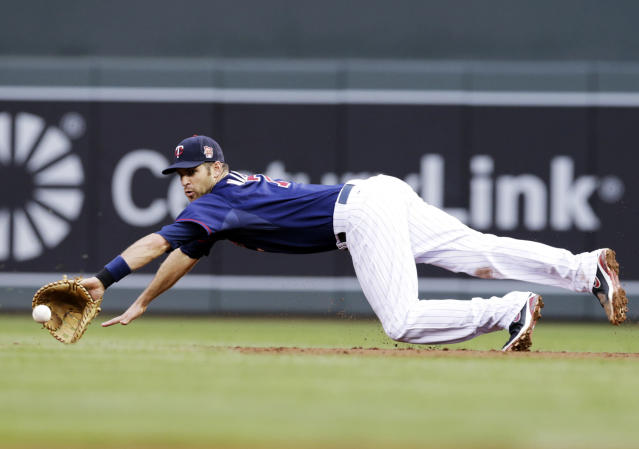 Minnesota Twins' Joe Mauer makes a diving stop of a ground ball by Texas Rangers' Adrian Beltre in the third inning of a baseball game Tuesday, May 27, 2014, in Minneapolis. Mauer relayed the ball to first base covered by pitcher Phil Hughes for the out. (AP Photo/Jim Mone)