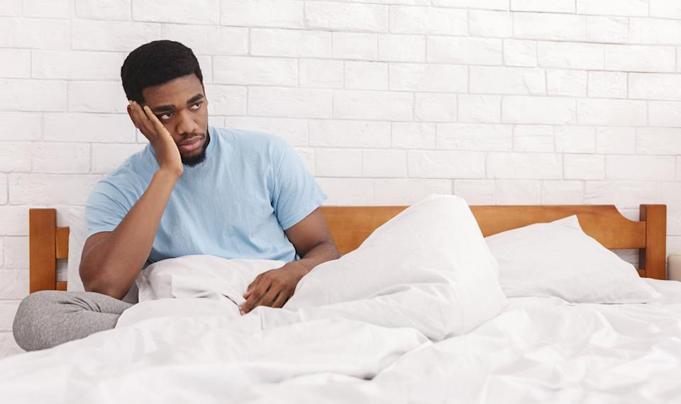Sad young black guy sitting in bed, thinking about relationship problems, considering breaking up with girlfriend, copy space